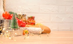 Christmas donations - food donations on light background with copyspace - pasta, fresh vegatables, canned food, baguette, cooking oil with Christmas decorations. Food bank. Selective focus
