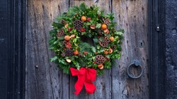 Christmas door wreath, a natural arrangement of flowers, berries, fruits and leaves fasten on a ring and set on a house entrance door as decoration, a winter holidays symbol of unending circle of life