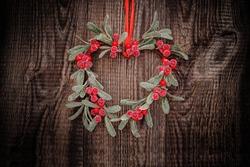 Christmas door wreath on wooden door. New Year mistletoe wreath. Christmas decorative green red mistletoe heart. Winter Christmas or New Year vintage Xmas card