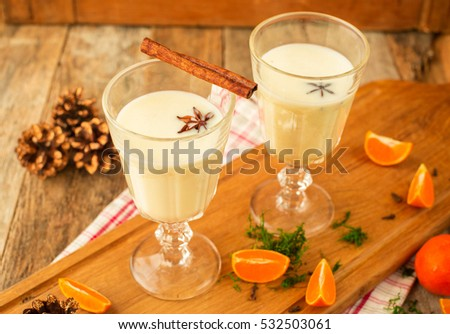 Christmas drink: eggnog with cinnamon and anise on wooden rustic background