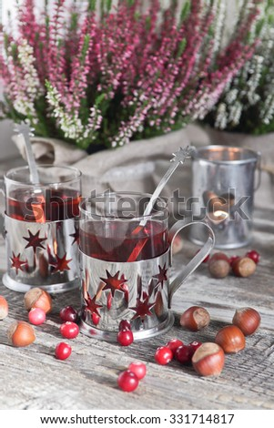 Christmas drink, heather, nuts, candle and cranberries on a wooden background #331714817