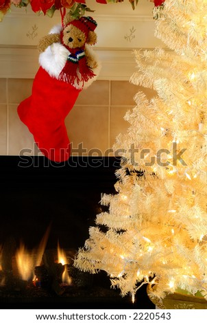 Christmas Eve - Red and white fur christmas stocking with a stuffed bear inside hangs on the mantle above the fireplace on Christmas Eve while a vintage white christmas tree sparkles in the night.