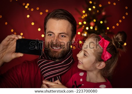 Christmas eve smiling father and daughter taking photo of themselves selfie on mobile phone Happy family time christmas tree with lights on dark red as background