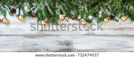 Christmas evergreen branches and golden ornaments on rustic white wood background #732474937