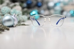 christmas eyeglasses blue spectacles isolated on white table with balls and decorations useful as a greeting gift card template with copy space
