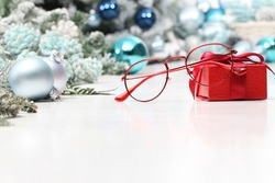 christmas eyeglasses red spectacles near package with ribbon bow isolated on white table with balls and decorations useful as a greeting gift card template with copy space