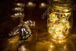 Christmas fairy lights in a mason jar, glowing in the dark, fairy lights in mason jar with selective focus, glitter overlay