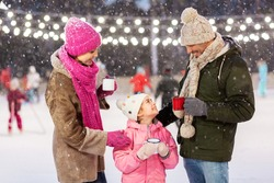 christmas, family and leisure concept - happy mother, father and daughter drinking hot tea at outdoor skating rink in winter