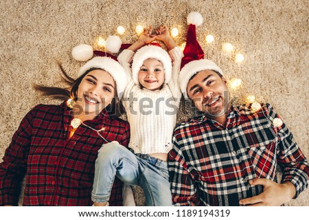 Christmas. Family. Happiness. Top view of dad, mom and daughter in Santa hats looking at camera and smiling while lying on the floor at home
