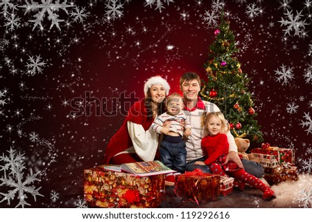 Christmas family of four persons and fir tree with gift boxes over red background