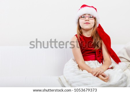 Christmas family time concept. Little girl looking like santas elf. Beautiful young lady wearing santa claus hat with white pompon. Small woman has red dress with bow and wears glasses. #1053679373