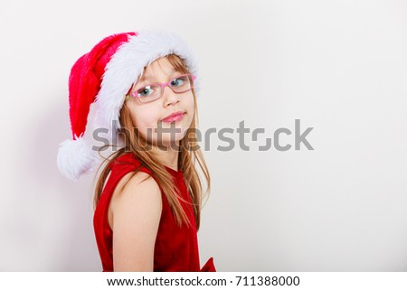 Christmas family time concept. Little girl looking like santas elf. Beautiful young lady wearing santa claus hat with white pompon. Small woman has red dress with bow and wears glasses. #711388000