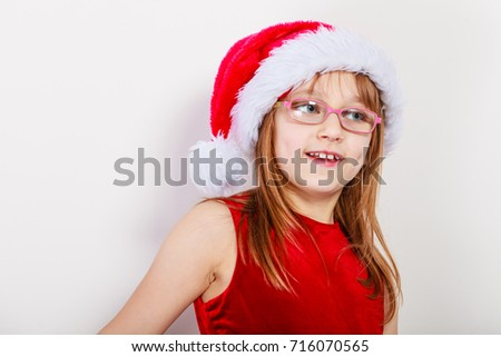 Christmas family time concept. Little girl looking like santas elf. Beautiful young lady wearing santa claus hat with white pompon. Small woman has red dress with bow and wears glasses. #716070565