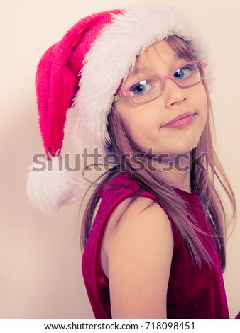 Christmas family time concept. Little girl looking like santas elf. Beautiful young lady wearing santa claus hat with white pompon. Small woman has red dress with bow and wears glasses. #718098451