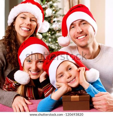 Christmas Family with Kids. Happy Smiling Parents and Children at home. Christmas Tree. Santa Hat