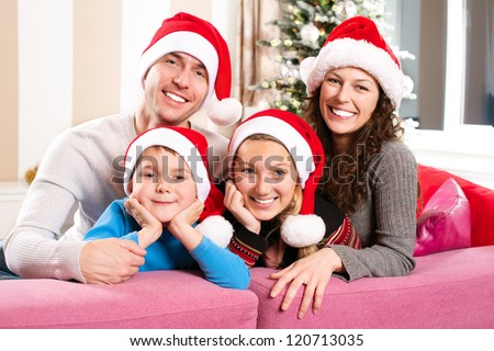 Christmas Family with Kids. Happy Smiling Parents and Children at home. Christmas Tree. Santa Hat.Father,mother,sister and brother Celebrating New Year together