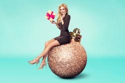 Christmas fashion photo of a nice woman sitting on a big gold christmas ball holding a christmas gift