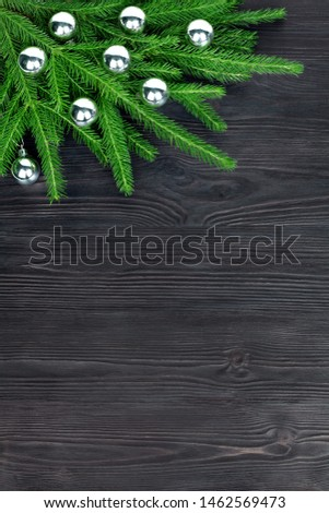 Christmas festive corner border, New Year decorative frame, silver glass balls decorations on green fir branches on dark black wooden background, winter holidays greeting card design, text copy space #1462569473