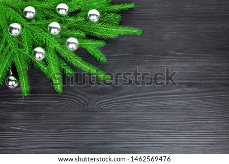 Christmas festive corner border, New Year decorative frame, silver glass balls decorations on green fir branches on dark black wooden background, winter holidays greeting card design, text copy space #1462569476