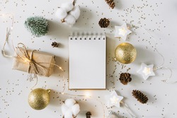 Christmas festive decorations and notebook. With wish list and 2021 goals concept. Notebook mock up, gift, and coton branch with shiny golden balls.New year flat lay, top view, copy space.