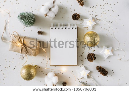 Photo of  Christmas festive decorations and notebook. With wish list and 2021 goals concept. Notebook mock up, gift, and coton branch with shiny golden balls.New year flat lay, top view, copy space.
