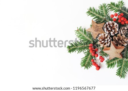 Christmas festive styled floral composition. Pine cones, fir tree branches, red rowan berries and wooden stars on white table background. Decorative frame, web banner. Flat lay, top view. Copy space.
