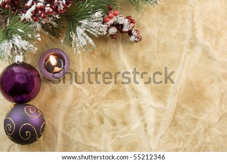 Christmas fir branch with purple tea light candle, baubles on antique paper with copyspace