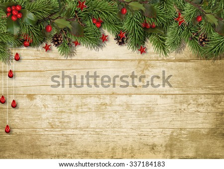 Christmas fir branches and holly on wood background #337184183