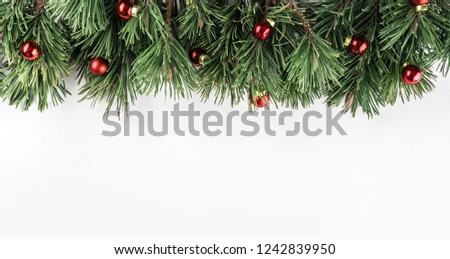 Christmas Fir branches with red decoration on white background. Xmas and Happy New Year theme. Flat lay, top view, wide composition #1242839950