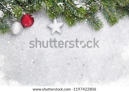 Christmas fir tree branch covered by snow and bauble decor on stone background. Xmas backdrop for your greeting card with space for text