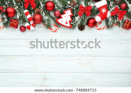 Christmas fir-tree branches with baubles and candies on wooden table #748884715