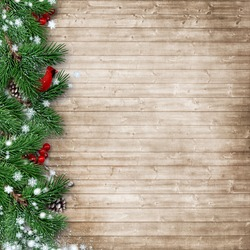 Christmas fir tree with a cardinal on a wooden background