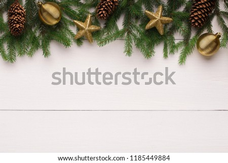 Christmas fir tree with golden stars and pine cones decoration on white wooden table, top view, copy space #1185449884