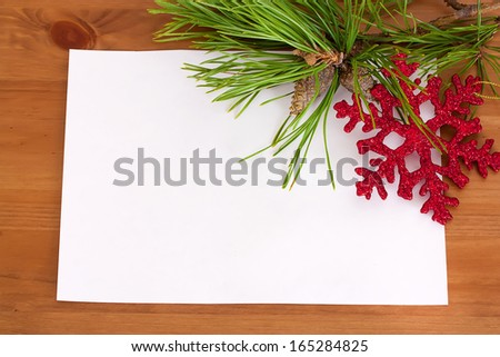 Christmas fir tree with paper and christmas decorations on wood background