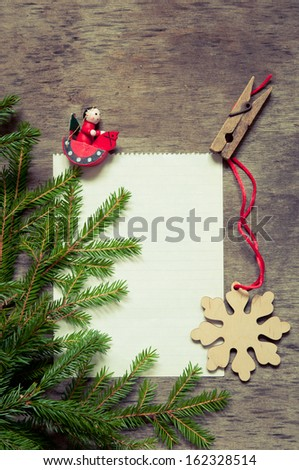 Christmas fir tree with paper and  decoration on a wooden board