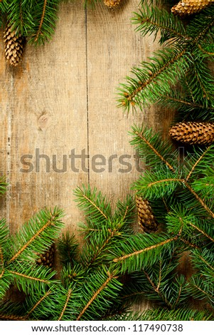 christmas fir tree with pinecones frame on a wooden board