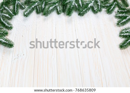 Christmas fir tree with snow on white wooden background. Free space frame #768635809