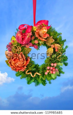 Christmas fir tree wreath decorated with fruits and flowers hanged over blue sky