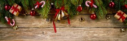 Christmas fir twigs ornamented with bells and baubles against wooden background