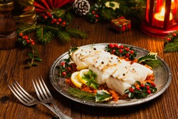 Christmas fish. Roasted cod pieces, served in vegetable sauce. Xmas styling. Front view.