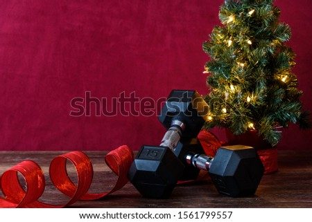 Christmas fitness, black dumb bells, with artificial Christmas tree and white lights, red ribbon, wood table, red background