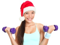 Christmas fitness sport woman wearing santa hat doing gym exercise training arms lifting dumbbells. Mixed race Chinese Asian Caucasian female fitness model isolated on white background.