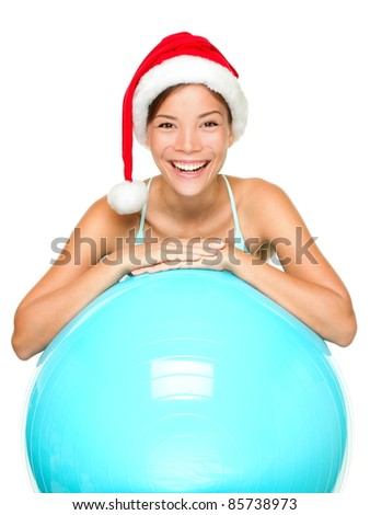 Christmas fitness woman on exercise ball wearing santa hat smiling joyful and happy. Beautiful cheerful mixed race Asian Caucasian female fitness model isolated on white background.