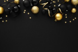 Christmas Flat Lay Background. Black Baubles on Dark Black Background. Minimalistic design. Copy Space. Horizontal.