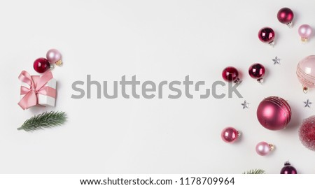Christmas flat lay scene with pink abd violet glass balls and gift box, copy space on white desk #1178709964