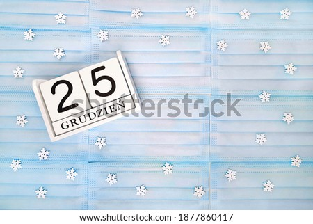Christmas flat lay with blue medical mask and white wooden block calendar. Date 25 December in polish language (grudzień). Snowflakes on background. Zdjęcia stock ©