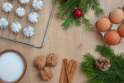 Christmas flat lay with cookies on gridiron, eggs, nuts, cinnamon and pine branch with pine cone