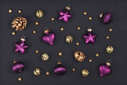 Christmas flat lay with elegant purple tree ornament baubles, golden fir cones and bells on dark black background