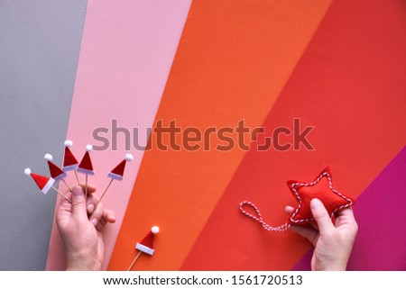 Christmas flat lay with female hands holding textile star and small santa hats. Top view of multicolored geometric layered paper background in red, orange, pink, magenta and silver layers from above. #1561720513