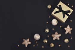 Christmas flat lay with golden gift box surrounded by shiny star, tree bauble and bell ornaments in corner of black background with empty copy space
